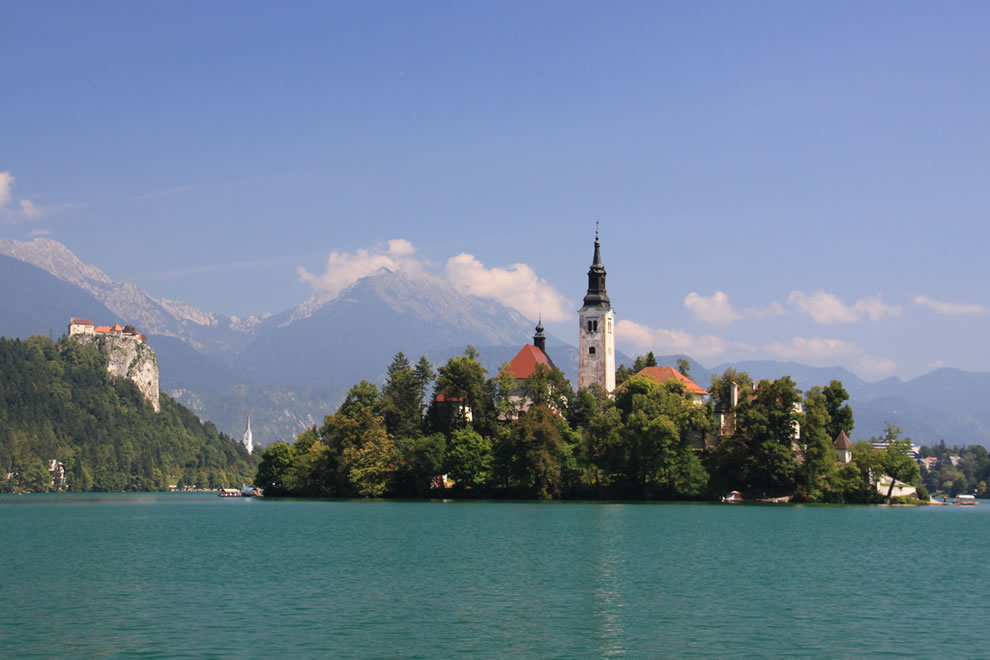 Church on small island in Lake Bled, with Castle on hillside