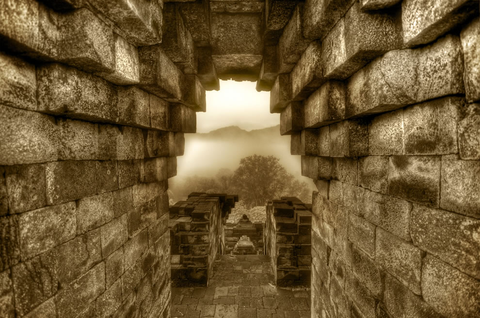 Archway overlooking the foggy jungles of Indonesia - Borobudur