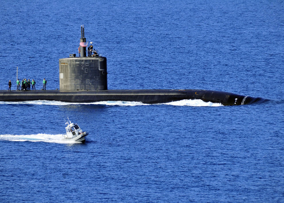 A harbor security boat escorts the Los Angeles-class attack submarine USS Annapolis (SSN 760) as the ship departs Souda Bay, Crete