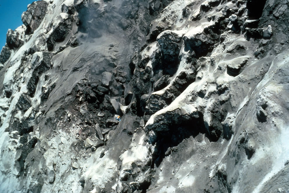 BEFORE View from helicopter of David Johnston near crest of the bulge on the north side of Mount St. Helens, sampling gases from fumaroles. David is near the center of the picture