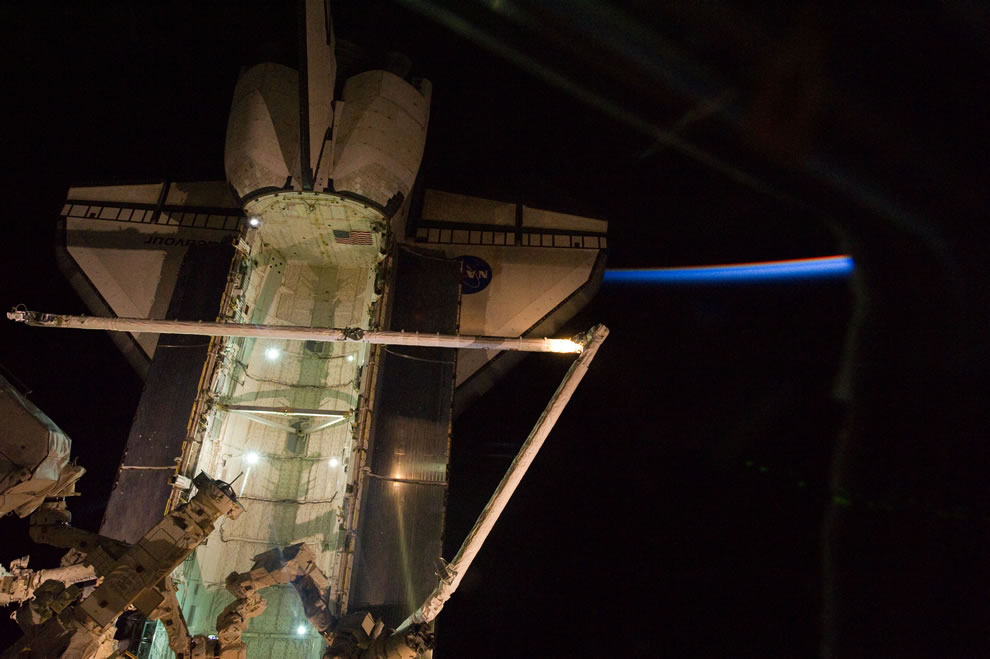Shuttle Endeavour docked to the ISS, backdropped by a thinly lit part of Earth's atmosphere and the blackness of orbital nighttime in space