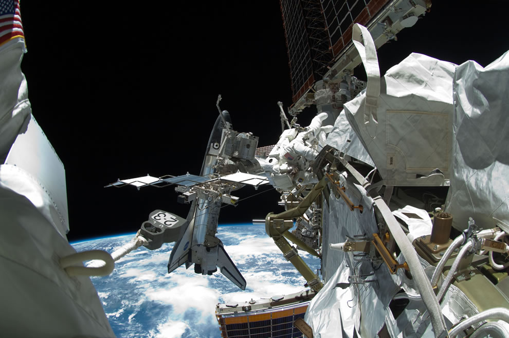 The docked space shuttle Endeavour is visible at left. The blackness of space and Earth's horizon provide the backdrop for the scene
