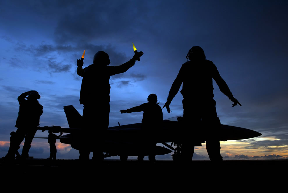 U.S. Navy aircraft director signals as aviation ordnancemen unload ordnance from an Super Hornet aircraft aboard the aircraft carrier USS Carl Vinson