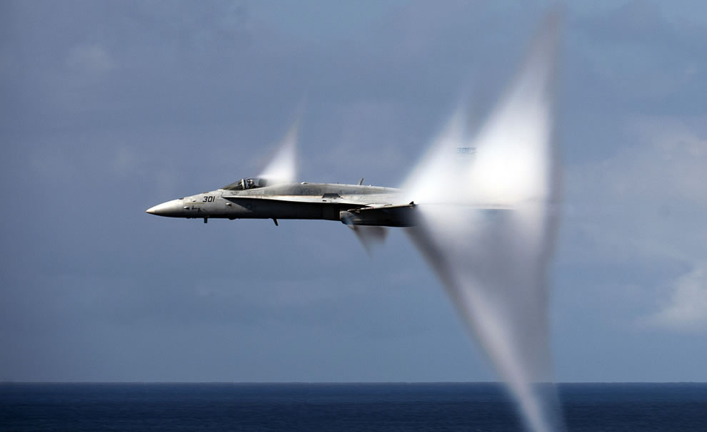 An F/A-18C Hornet assigned to Strike Fighter Squadron (VFA) 113 breaks the sound barrier during an air power demonstration over the Nimitz-class aircraft carrier USS Carl Vinson
