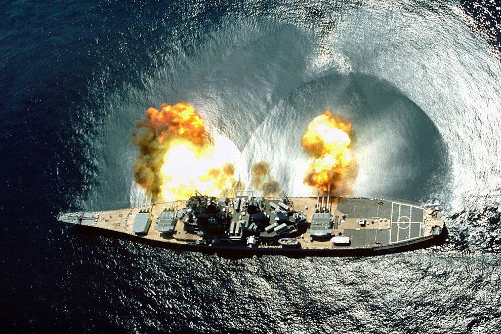 SS Iowa (BB-61) fires a full broadside of her nine guns during a target exercise near Vieques Island, Puerto Rico- Note concussion effects on the water surface, and 16-inch gun barrels in varying degrees of recoil