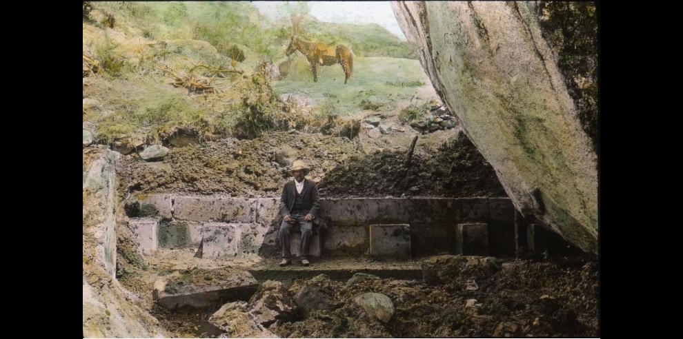A man in 1911 sitting on Incan ruins in Peru