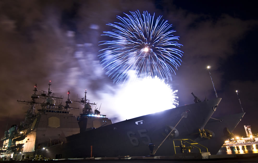 Fireworks at the Joint Base Pearl Harbor-Hickam explode over two Aegis-class cruisers, USS Chosin and USS Lake Erie