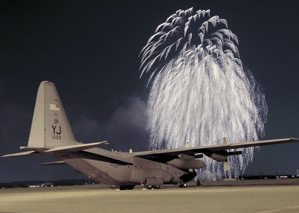 Fireworks erupt in front of a C-130 Hercules on the flightline at Yokota Air Base, Japan, at the Independence Day festivities
