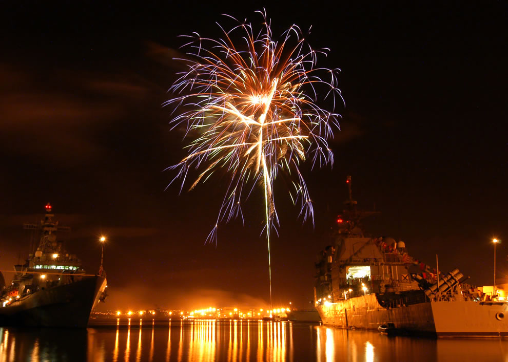 Fireworks explode over the guided missile cruiser USS Champlain and Republic of South Korean destroyers Yi  and Ulchimoonduk