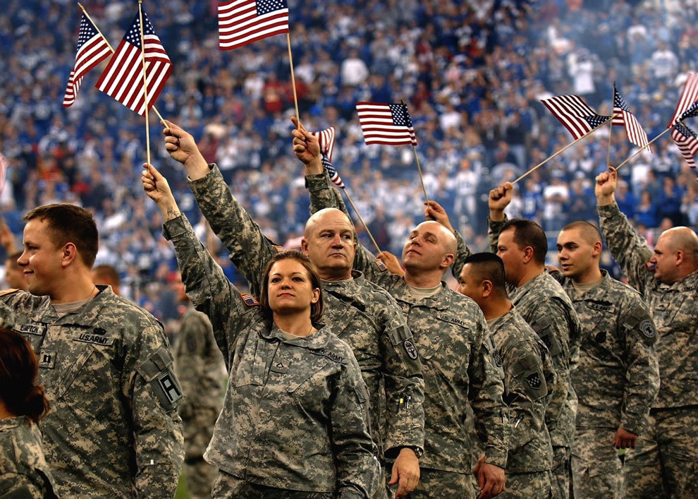 Soldiers wave American flags as they are recognized at the RCA Dome in Indianapolis - Independence Day