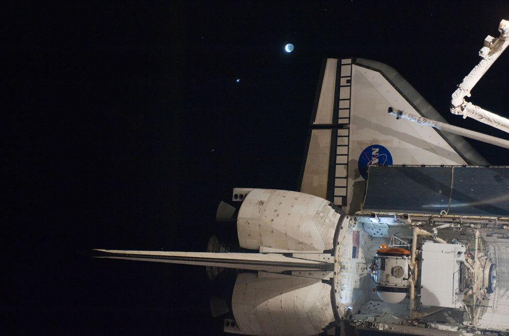 The planet Venus, the moon and the aft section of space shuttle Atlantis