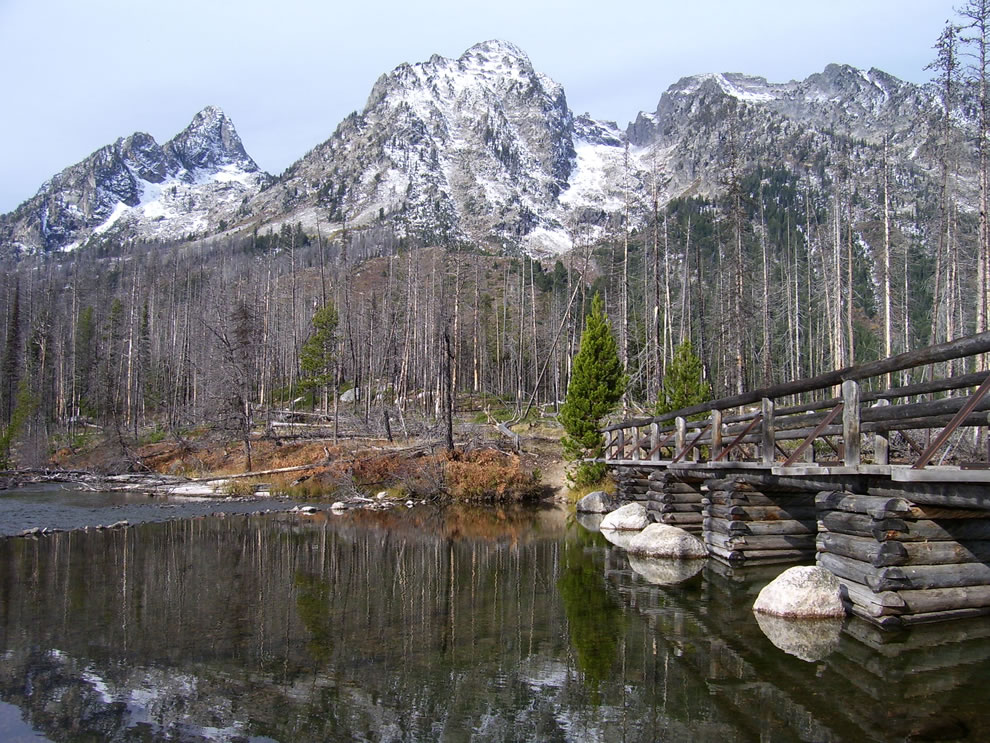 New snow and reflection in String Lake and wooden bridge with Grand Teton in background