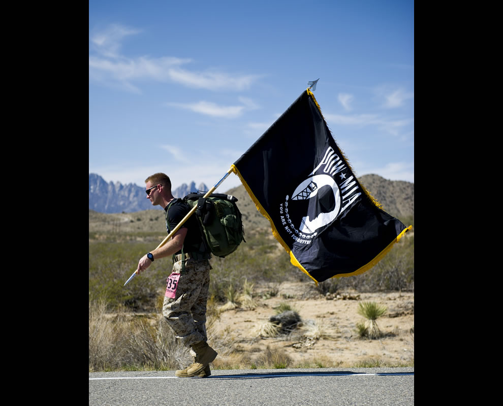 A participant in the Bataan Memorial Death March carries a prisoners of war and missing in action flag along the course at the White Sands Missile Range, N.M