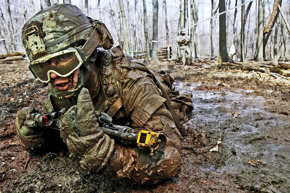 Crawling through mud, solider searches for the next covered fighting position