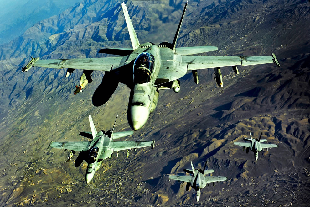 Four U.S. Navy FA-18 Hornet aircraft fly over mountains during a mission in Afghanistan