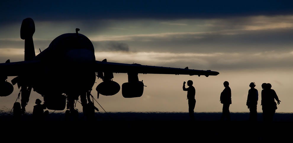 U.S. Sailors with Electronic Attack Squadron 131 perform final checks on an EA-6B Prowler aircraft on the flight deck of the aircraft carrier USS Abraham Lincoln