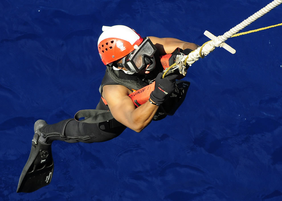 search and rescue swimmer assigned to the amphibious transport is lowered from the forecastle
