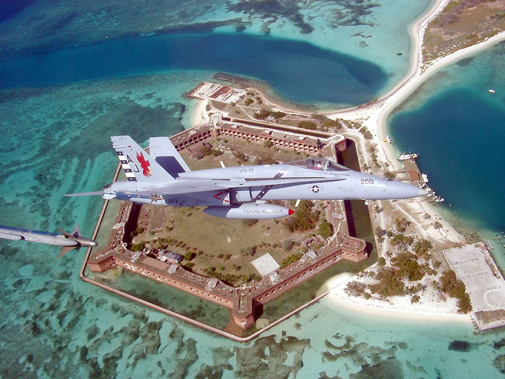 Navy Lieutenant Luke Kremer pilots his FA-18 C 'Hornet' strike fighter from the 'Fighting Redcock' of Strike Fighter Squadron Two Two (VFA-22) over the Fort Jefferson National Monument
