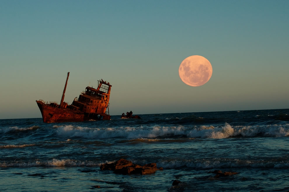 Full moon and one of the shipwrecks rusting into the sands of Necochea, on the Argentine coastline