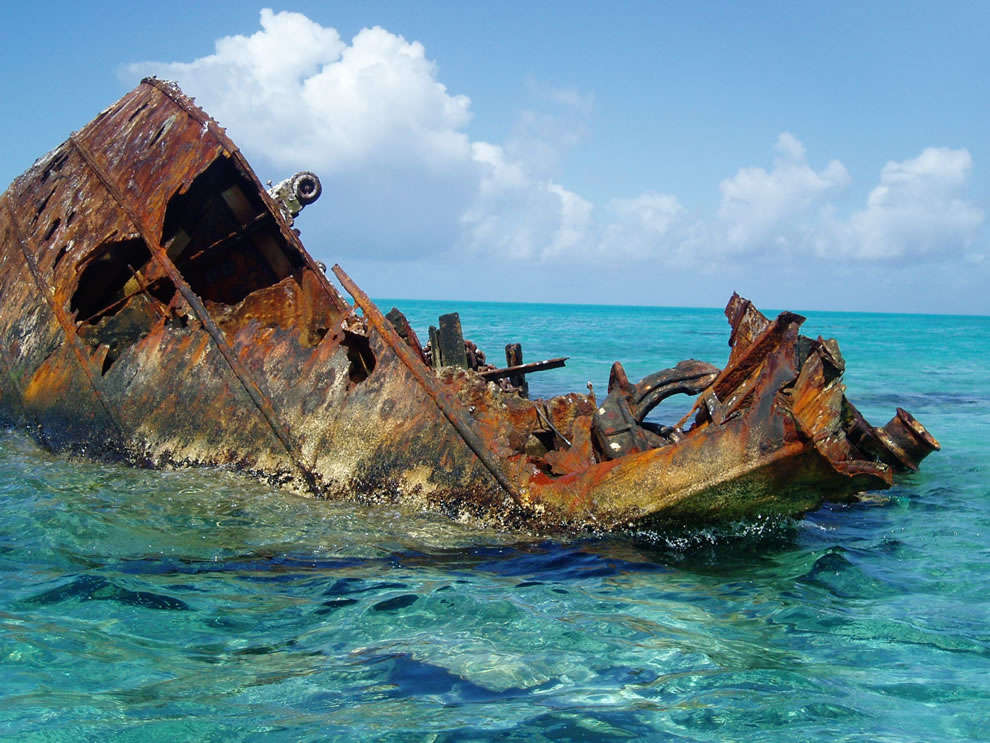 Rusted shipwreck resting on a reef in Hawaii - All that remains above water of an unnamed vessel wrecked on the reef long ago