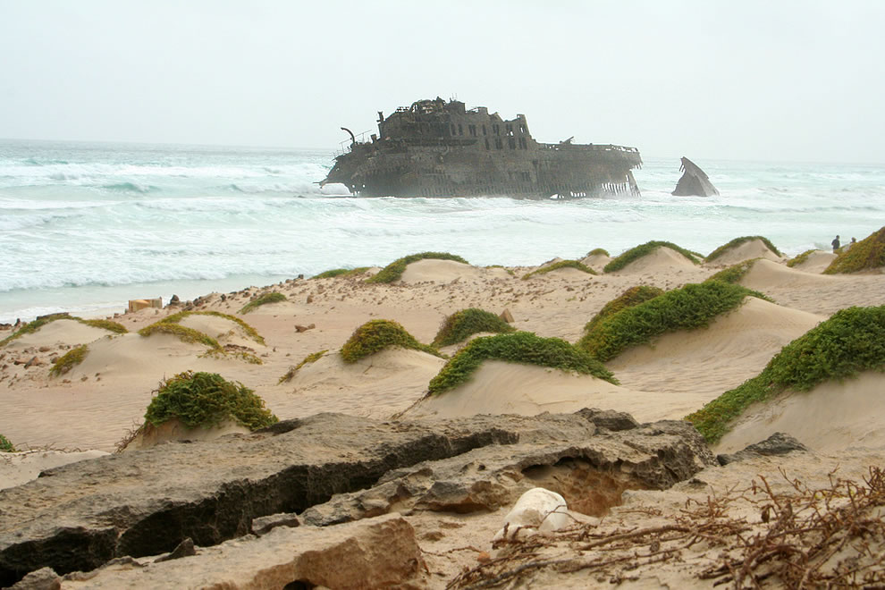 Shipwrecked Santa Maria, a rusty crusty 40 year old relic, decaying in the distance of dunes on the beach, waves in the sea, a few miles from the island capital Sal Rei on Boa Vista, Cape Verde
