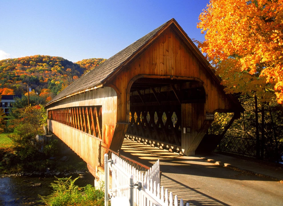Covered wooden bridge with hilly woods bright with autumn colors
