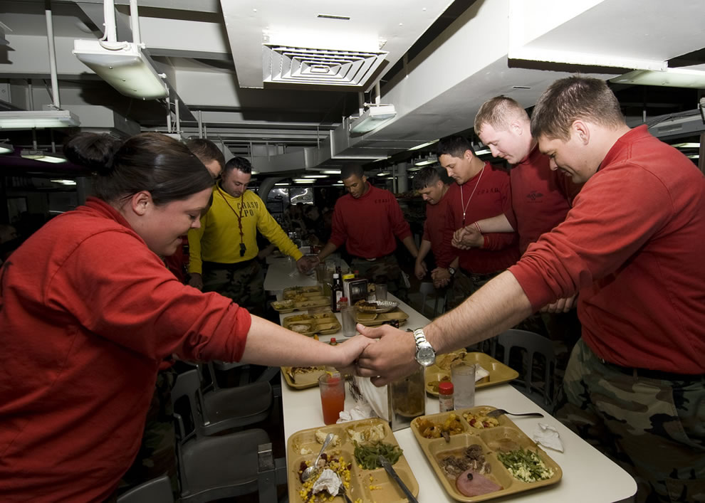 Sailors give thanks before enjoying their Thanksgiving