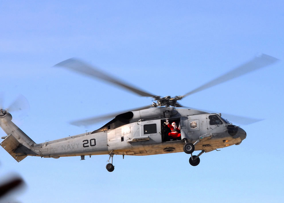 Santa Claus flies in an SH-60F Sea Hawk helicopter