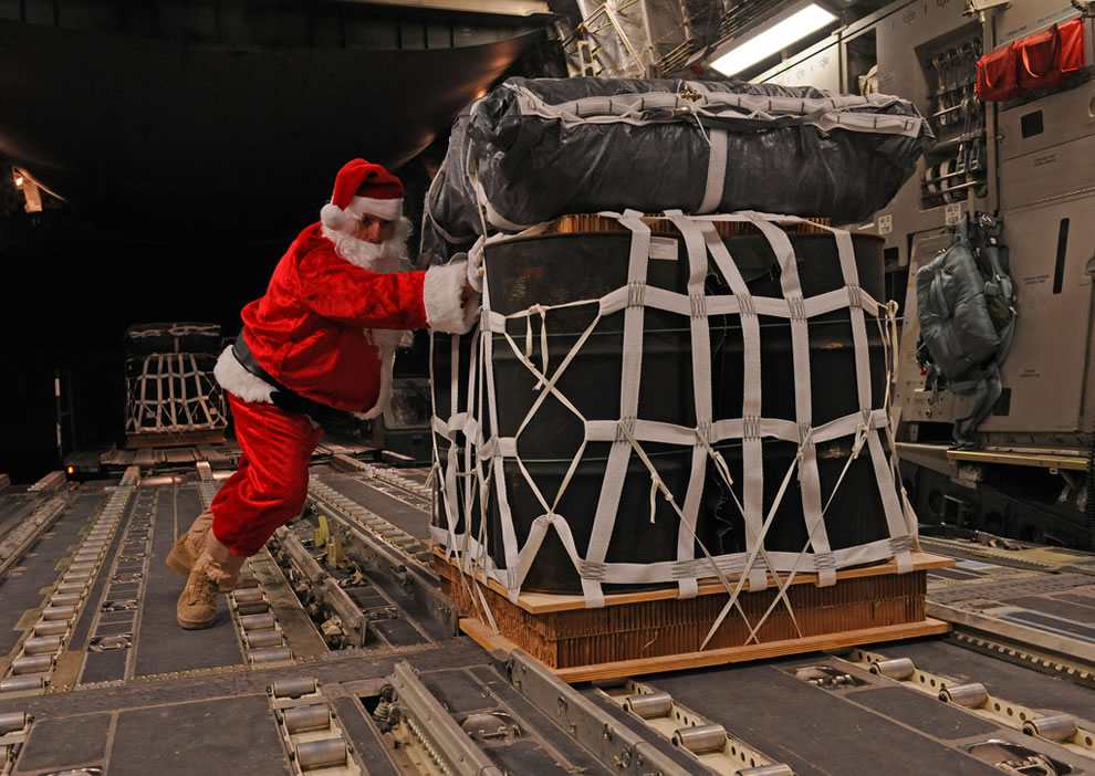 dressed as Santa Claus while loading a pallet of fuel onto a C-17 Globemaster III aircraft prior to a mission from an undisclosed location in southwest Asia