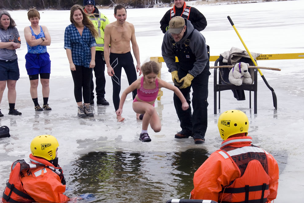 Hole cut in the ice of North Bar Lake, Empire, Michigan, as young girl takes the polar bear plunge