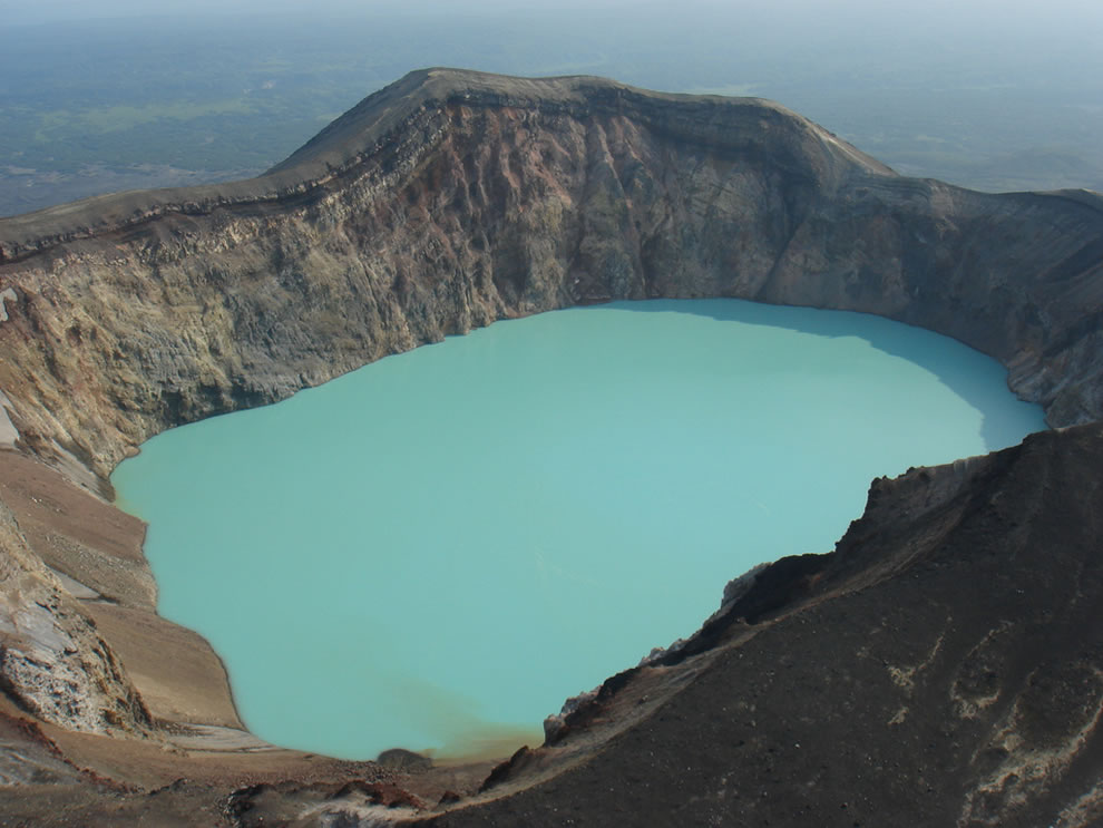 Maly Semiachik volcano - crater lake. Kamchatka Peninsula, Far East Russia. Pale blue water fills the lake. The colour may be due to fine silica particles