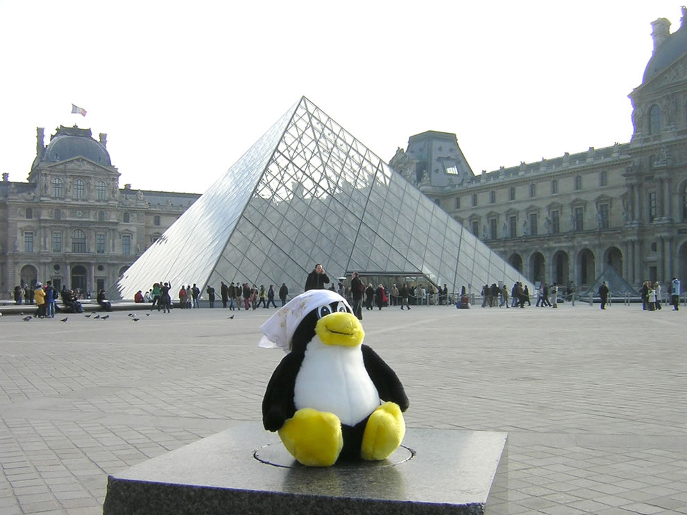 Tux in front of The Louvre Pyramid which is the main entrance to the Louvre Museum in Paris