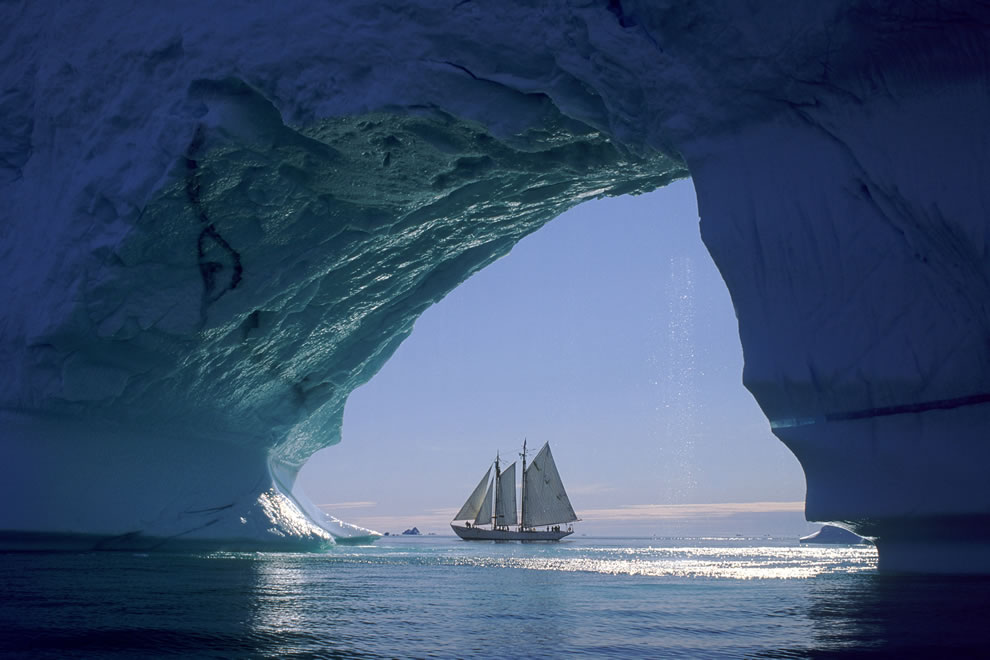 Sailboat seen through huge iceberg cave