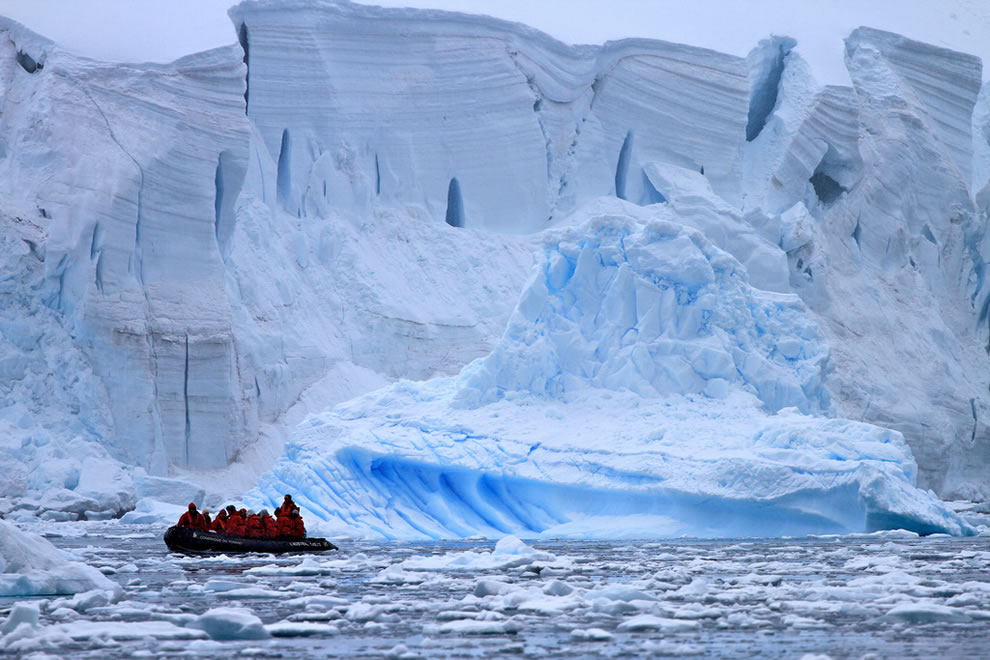 Small boat in ice near immense icebergs in Antarctica