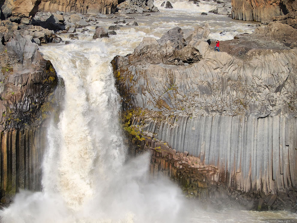 Aldeyjarfoss waterfall against basalt columns and person to give an idea of its size