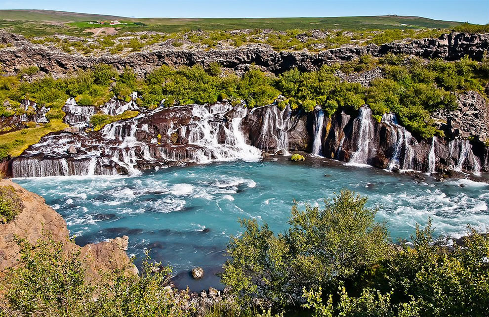 In western Iceland, water flows through a lava field and emerges to form a series of about 2953 ft (900 m) waterfalls called Hraunfossar