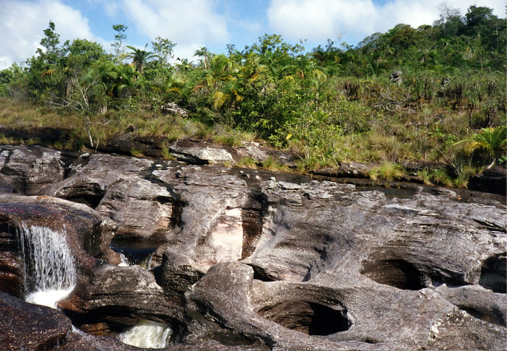 Small circular pits called giant's kettle in the rocky Caño Cristales river bed