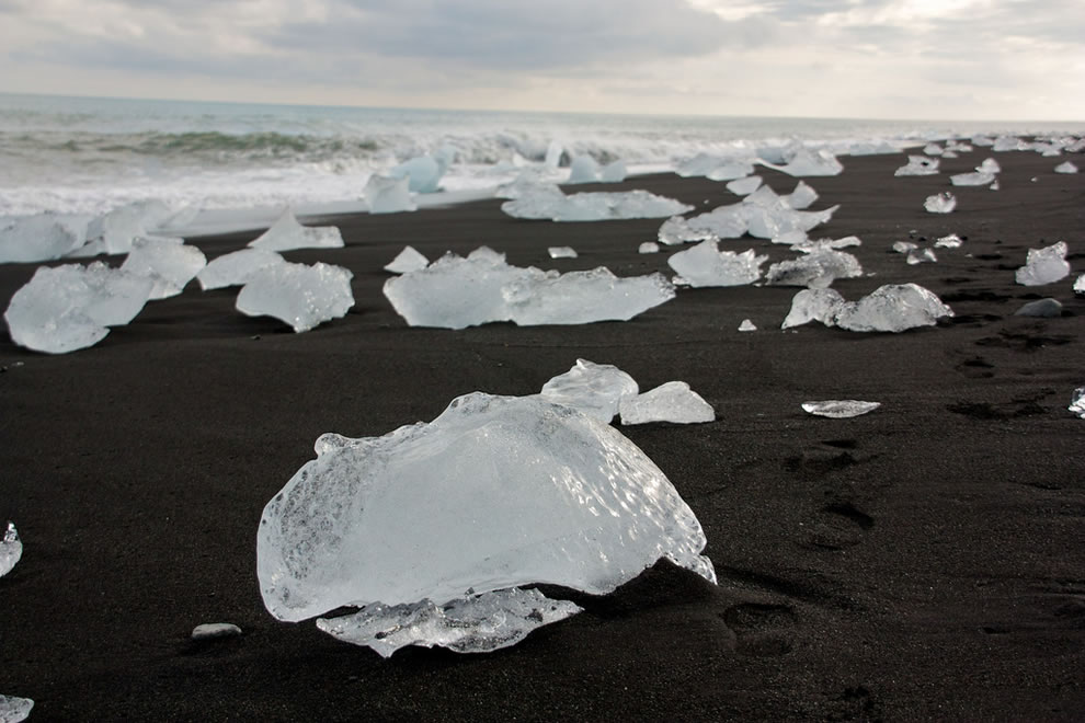 Icebergs from the Jökulsárlón glacier lagoon wash ashore, black sand beach in Iceland