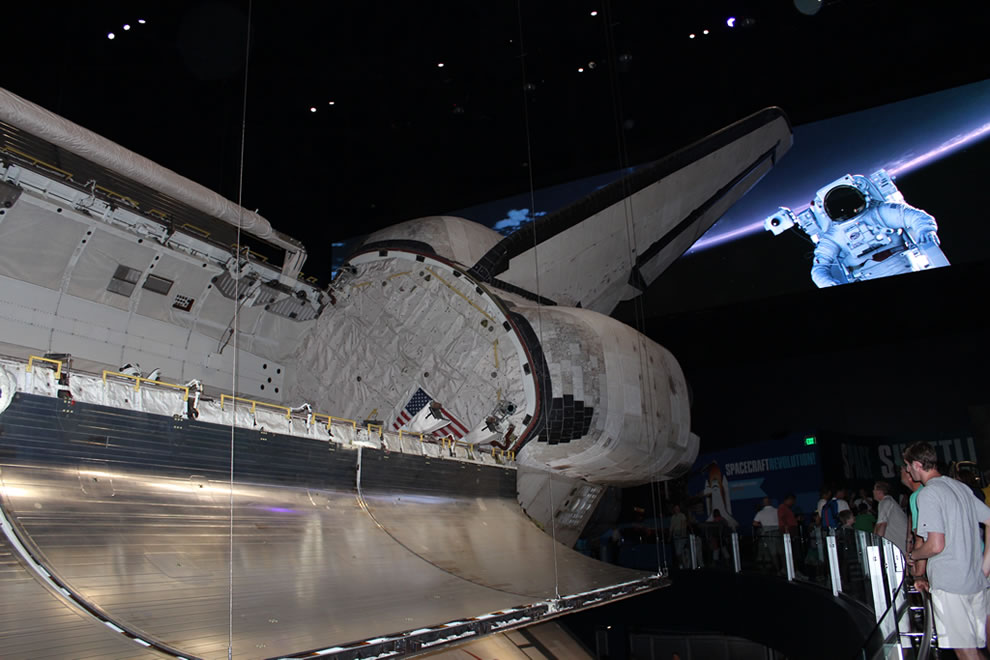 Atlantis space shuttle payload doors open with astronaut behind her