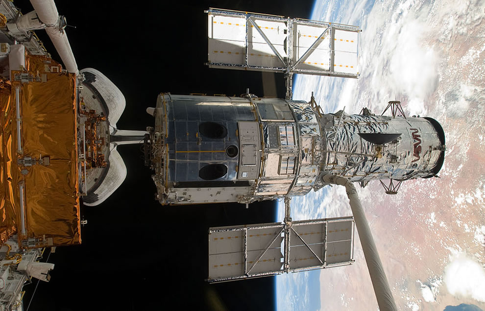 The Hubble Space Telescope lifted out of the payload bay of Atlantis, moments before it is released into space following the successful repair mission of STS-125