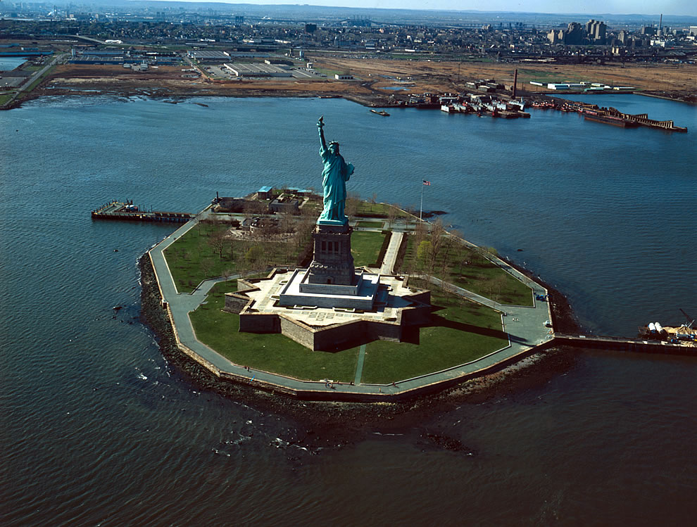 1984 before scaffolding surrounded the statue, overall view of Liberty Island looking northwest with Jersey City in the background