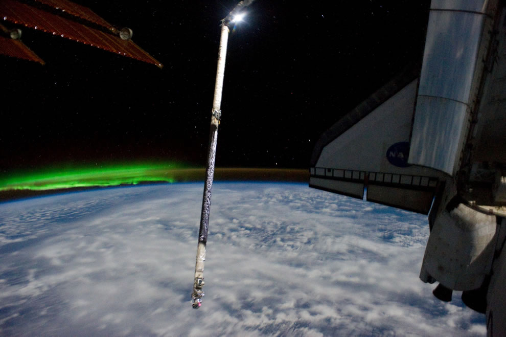 Atlantis, payload bay doors open, NASA emblem on her wing with aurora seen from space via ISS on July 26, 2011
