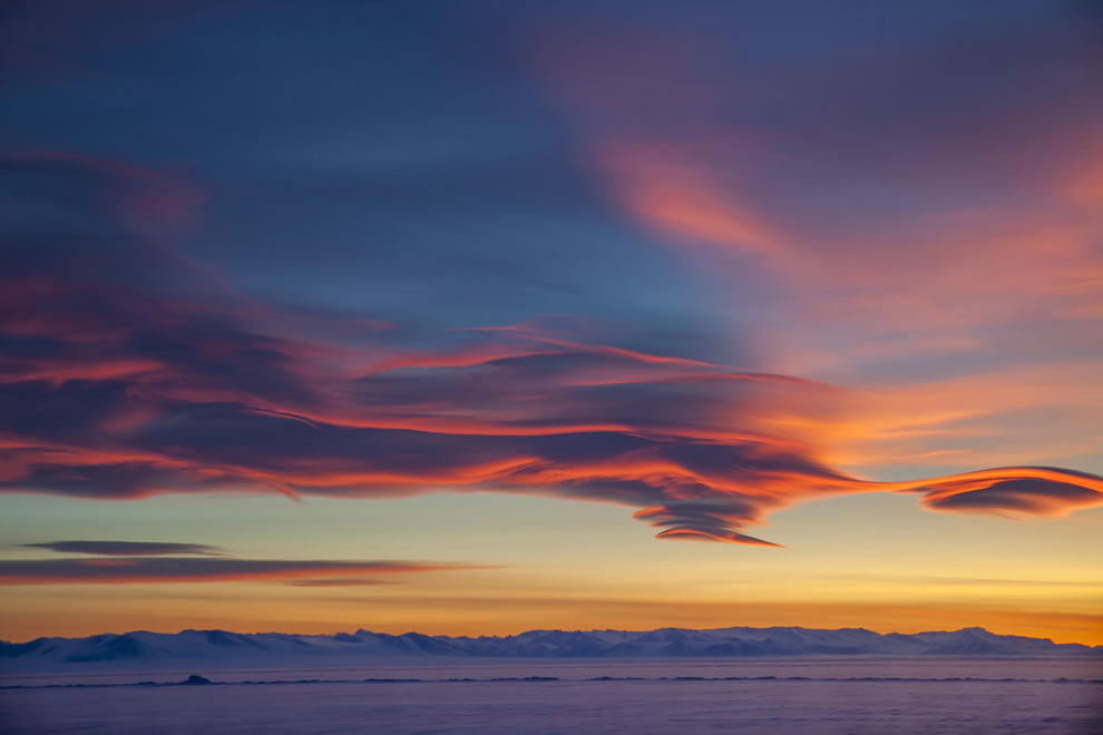 Lenticular clouds hang steady over the sea ice in McMurdo Sound