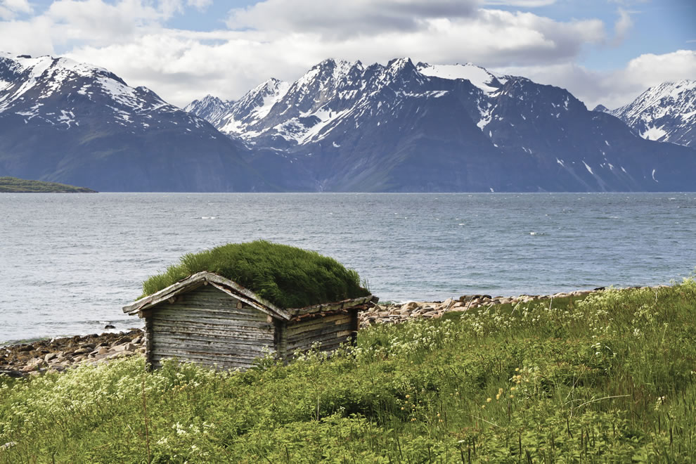 A shed with a green roof at the east coast of Lyngen fjord in Troms, Norway