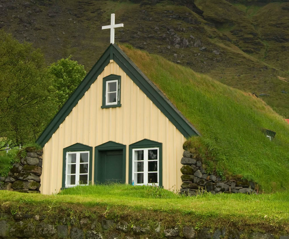 Icelandic Church with turf roof, as the mist descends from the mountains