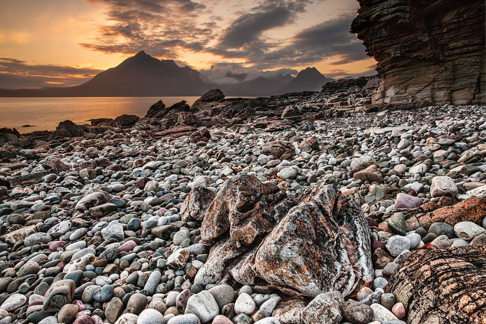 Rocky beach and The Cuillin mountain range at sunset