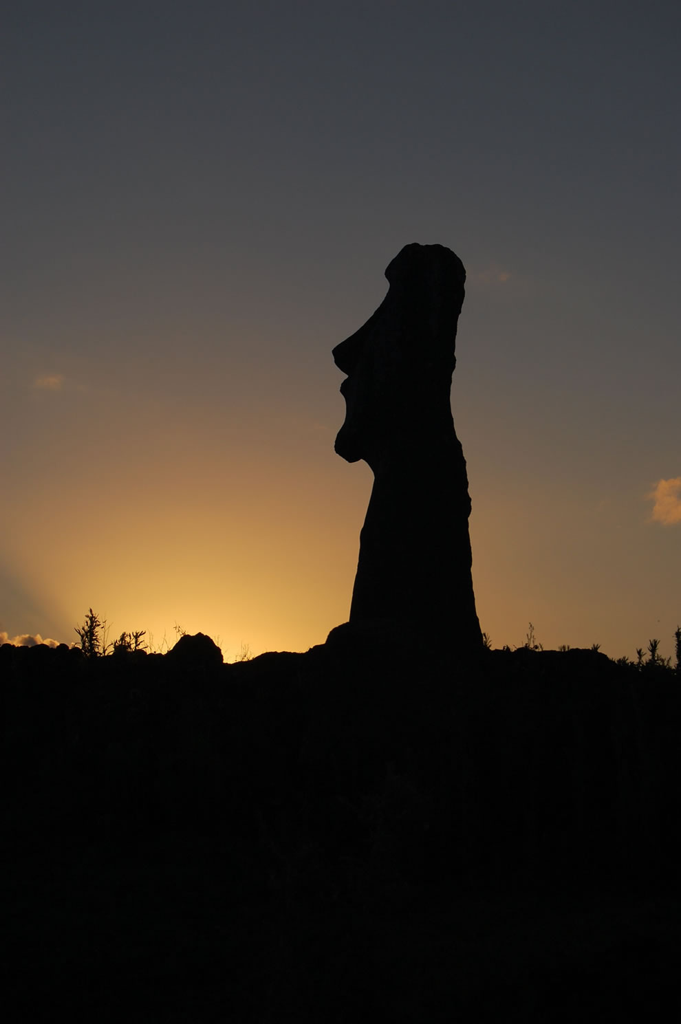 A moai silhouetted in one of the thousands of sunsets that have occurred since its being placed on the rocky shores of Easter Island