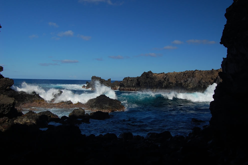 Easter Island - A small hole-in-the wall affords a glimpse of azure surf pounding against against jagged volcanic rocks