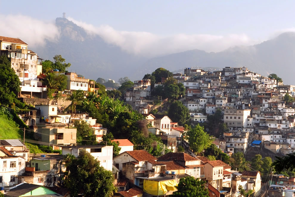 Rio de Janeiro slum (right) on hill contrasted with a more affluent neighborhood, as viewed from a tram in Santa Teresa; Cristo Redentor (christ statue) is in the left background
