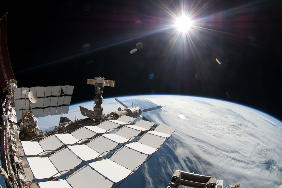 Endeavours final spacewalk - A bright sun, a portion of the International Space Station and Earth's horizon
